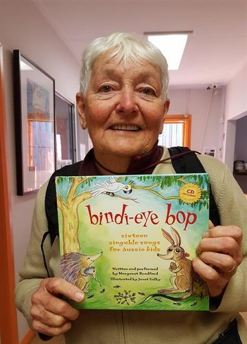 "Margaret Bradford pictured with her eco-friendly picture book and CD for kids ""Bindi-Eye Bop"" Margaret is a teacher and a well-known folk singer and songwriter."